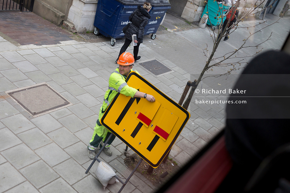 A roadworks workmen swaps signpost arrows telling motorists about lane closures during roadworks at Lambeth North in Southwark, on 28th March 2019, in London, England