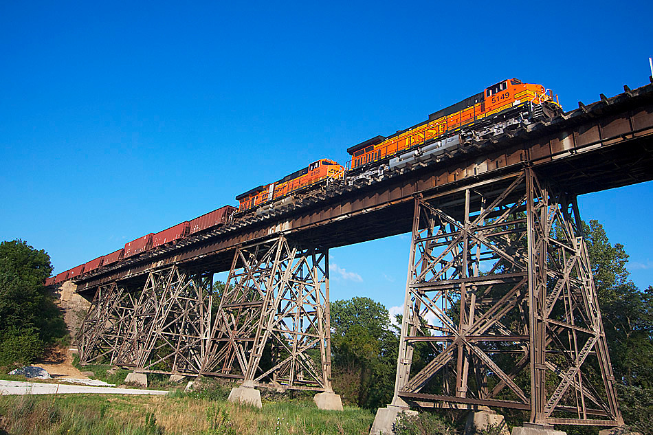 High above a small creek, a BNSF freight train crosses the Media trestle near Media, IL on the former Santa Fe Chillicothe Subdivision, heading for Fort Madison, IA. This massive steel structure was built in the early 1900s.