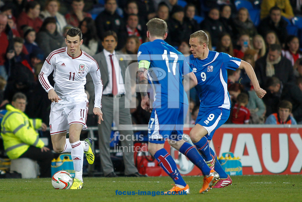 Gareth Bale of Wales and Kolbein Sigthorsson of Iceland during the International Friendly match at the Cardiff City Stadium, Cardiff<br /> Picture by Mike  Griffiths/Focus Images Ltd +44 7766 223933<br /> 05/03/2014