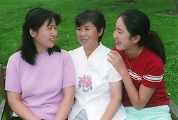 Three generations of woman members of a family chatting together,