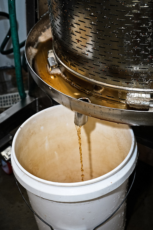 Cider drains out of slats in the cider press into a barrel placed underneath the tap.