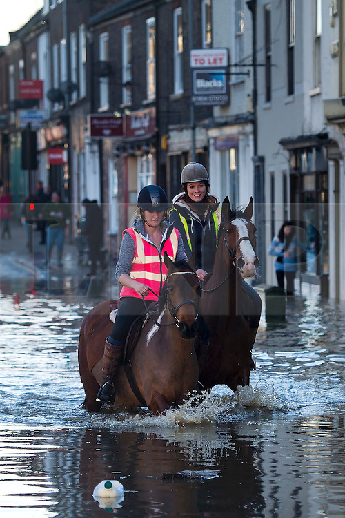 © Licensed to London News Pictures. 27/12/2015. York, UK.  Two young women ride their horses through flood water in York city centre. Large areas of the North of England have been hit by severe flooding following unusually heavy rainfall in December. Photo credit: Ben Cawthra/LNP