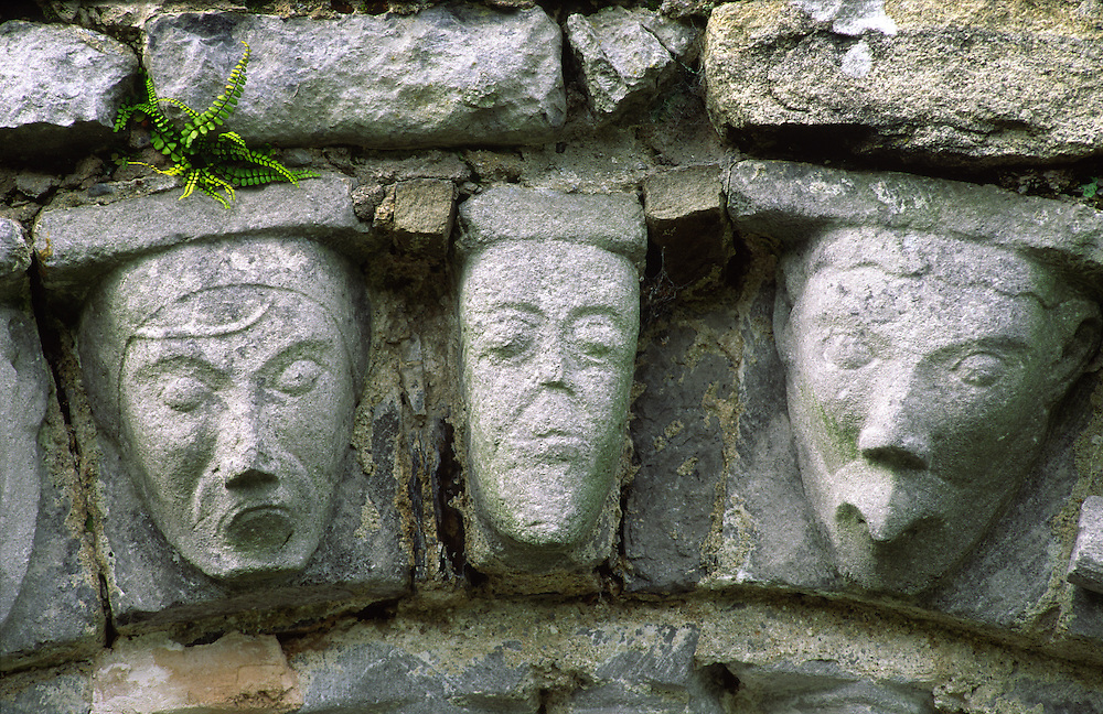 Carved stone human and animal heads on Romanesque door arch of ancient monastic church at Dysert O'Dea, County Clare, Ireland.