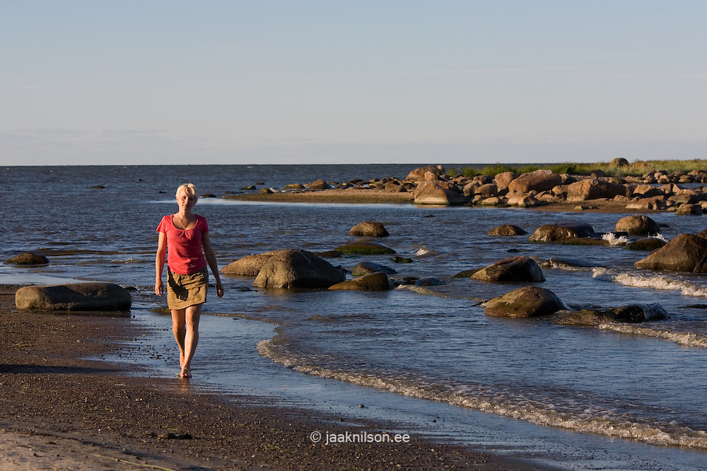 Young Woman Walking in Water by Baltic Sea Stony Coast near Kalvi, Ida-Viru County, Estonia