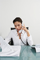 Woman using telephone at desk in office