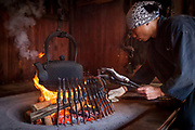 Roasting trout on fire, Myojin mountain lodge Kamikochi, Chubusangaku National Park, used by Rev Walter Weston in 1890s, pioneer of mountaineering in Northern Japan Alps