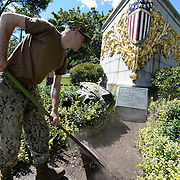BANGOR Maine,  -- 8/8/15 - A US Navy Reservist rakes mulch over a section of path at the USS Maine (ACR 1) Memorial in downtown Bangor on Saturday. Phillips, and four fellow reservists from Navy Operational Support Center, Bangor, spent the afternoon spreading mulch around the memorial's pathways. USS Maine, an armored cruiser commissioned in 1895, sank in Havana harbor in 1898, just prior to the Spanish-American War.