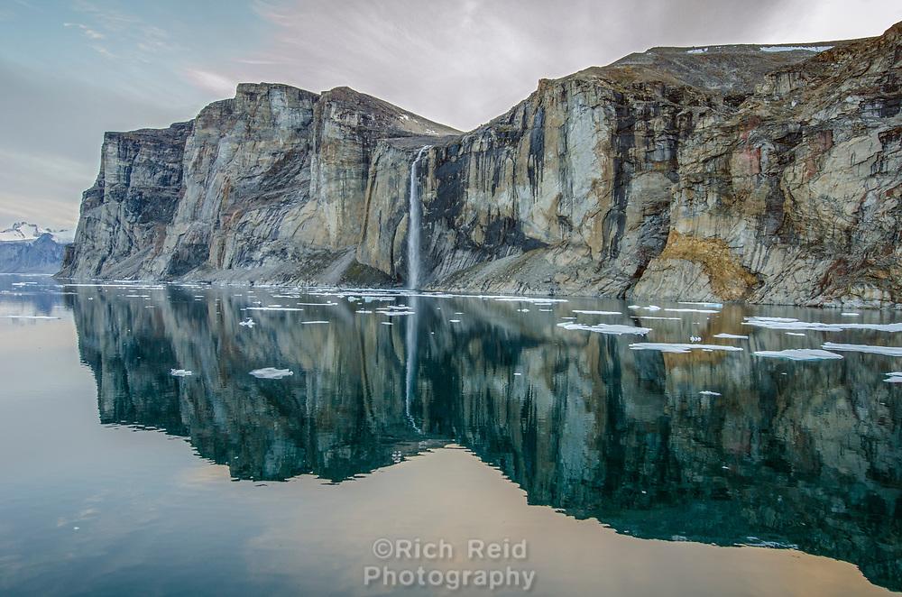 Waterfall cascading into Baffin Bay from Scott Island off Baffin Island, Nunavut, Canada.