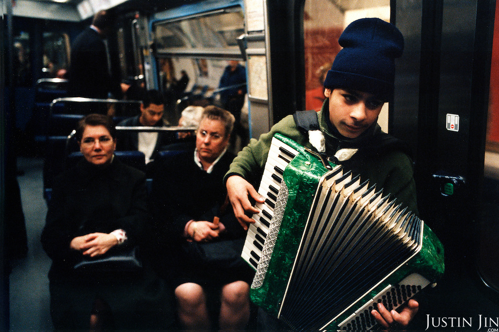 A young Roma busker plays instrument in Paris metro..Picture taken 2005 by Justin Jin