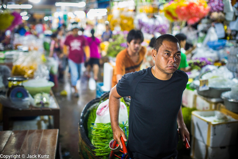 19 OCTOBER 2012 - BANGKOK, THAILAND: A porter pulls his hand truck through the Bangkok Flower Market. The Bangkok Flower Market (Pak Klong Talad) is the biggest wholesale and retail fresh flower market in Bangkok.  The market is busiest between 3:30AM and 6AM. Thais grow and use a lot of flowers. Some, like marigolds and lotus, are used for religious purposes. Others are purely ornamental.           PHOTO BY JACK KURTZ