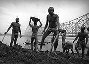 Calcutta, India.  Business men.  In the early morning.  Rub sand on themselves.  Religious practice.  Hindus.  Go down to the river. Early morning.