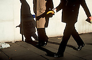A businessman strides along a London street holding a banana whose shadow appears to be part of another man's penis (from a film original).