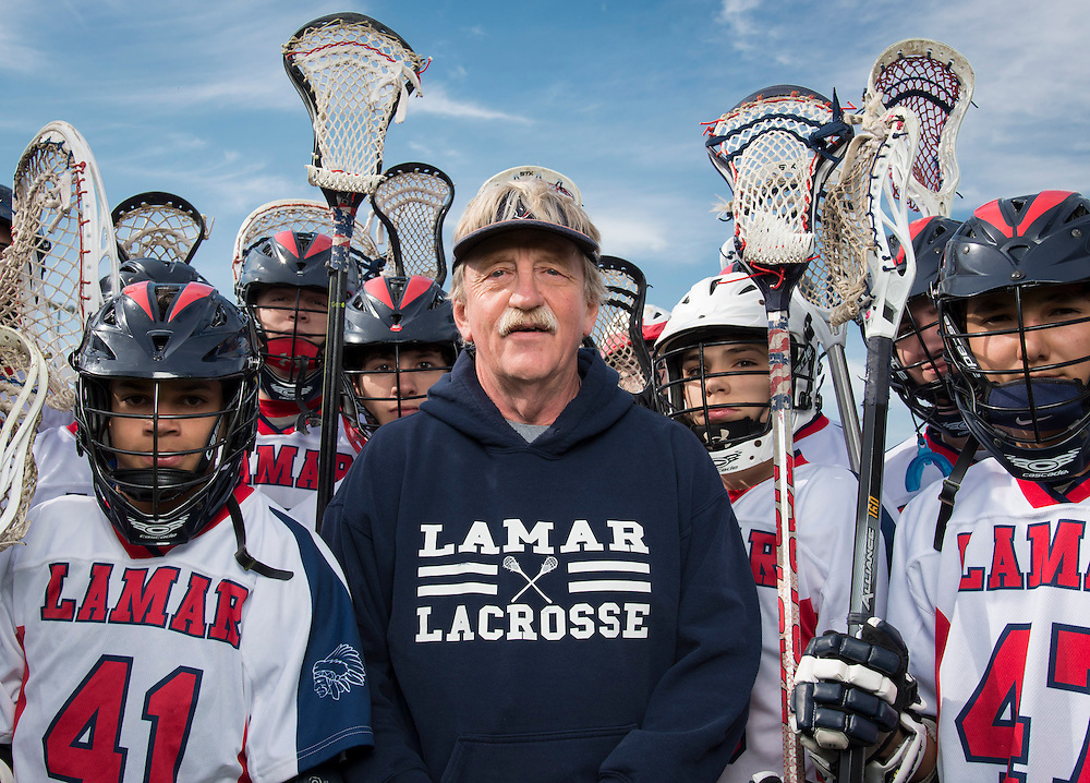 Houston ISD senior manager for IT Dave Vollmer poses with Lamar High School lacrosse players, March 25, 2014. Vollmer has been coaching Lamar lacrosse for 26 years.