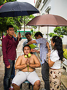"""21 JULY 2013 - BANGKOK, THAILAND:   A young man's family cuts his hair under an umbrella during a rain before he became ordained as a Buddhist monk at Wat Benchamabophit on the first day of Vassa, the three-month annual retreat observed by Theravada monks and nuns. Men frequently enter the monastery and become monks for Vassa. On the first day of Vassa (or Buddhist Lent) many Buddhists visit their temples to """"make merit."""" During Vassa, monks and nuns remain inside monasteries and temple grounds, devoting their time to intensive meditation and study. Laypeople support the monastic sangha by bringing food, candles and other offerings to temples. Laypeople also often observe Vassa by giving up something, such as smoking or eating meat. For this reason, westerners sometimes call Vassa the """"Buddhist Lent.""""      PHOTO BY JACK KURTZ"""