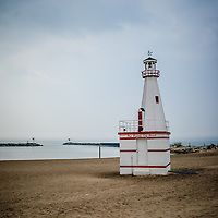 Photo of the New Buffalo lighthouse in New Buffalo Michigan with the beach and Lake Michigan.