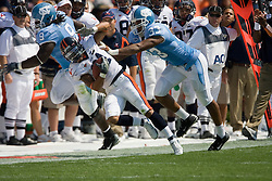 Virginia wide receiver Andrew Pearman (21) is pushed out of bounds by North Carolina defensive end Hilee Taylor (33).  The North Carolina Tar Heels football team faced the Virginia Cavaliers at Kenan Memorial Stadium in Chapel Hill, NC on September 15, 2007.  UVA defeated UNC 22-20.