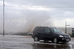 © Licensed to London News Pictures. 03/02/2014. Exmouth, UK. Waves crash over the seawall. Seawater floods the seafront in Exmouth Devon.The water breached defences and flooded Morton Road, St Andrews Roads, Victoria Road and some of the other surrounding streets. Police closed the road to vehicles. Officials were seen delivering sandbags to the local residents. . Photo credit : Russ Nolan/LNP