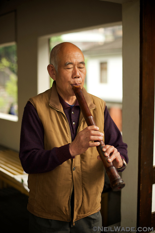 A man plays a Chinese bamboo flute in front of the Beitou Hot Spring Museum.