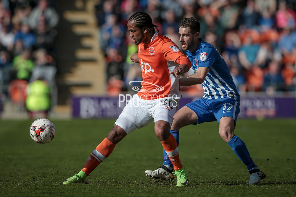 Nathan Delfouneso (Blackpool) and Nicky Deverdics (Hartlepool United) go for the ball during the EFL Sky Bet League 2 match between Blackpool and Hartlepool United at Bloomfield Road, Blackpool, England on 25 March 2017. Photo by Mark P Doherty.