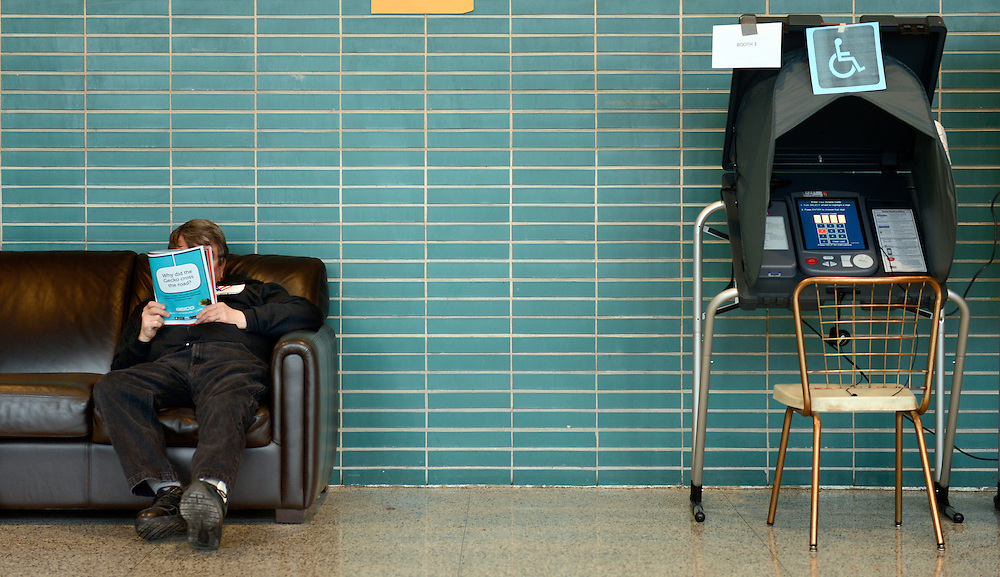 Republican verification judge Cliff Mayoh reads a magazine to pass the time alongside the empty voting booths Tuesday with light voter turnout at Precinct 1 at Trewyn School for the Peoria municipal primary election. Weather became a factor early with snow, sleet and rain hindering voters.