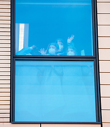 © Licensed to London News Pictures; 30/04/2020; Bristol, UK. Hospital staff are seen waving and clapping at the windows of the Intensive Care Unit at Southmead Hospital as Emergency Service workers and the public clap outside Southmead Hospital at 8pm on Thursday evening to applaud NHS health service workers during the coronavirus Covid-19 pandemic. Photo credit: Simon Chapman/LNP.