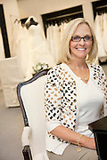 Portrait of a happy senior female wearing eyeglasses sitting in bridal boutique