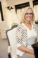 Portrait of a happy senior female wearing eyeglasses sitting in bridal boutique