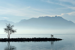 © Licensed to London News Pictures. 08/12/2016. Annecy, Haute Savoie, France. Two young female joggers take a break on a peninsula at Lake Annecy, Savoie, France. Lake Annecy is shrouded in mist and air  pollution which has been trapped under the temperature inversion layer. The temperature inversion is a result of a large high pressure system sitting over France - and most of Europe. This has caused the highest air pollution levels in Paris for ten years. Traffic is being regulated in Paris and Lyon, France because of the high levels of air pollution. Photo credit: Graham M. Lawrence/LNP