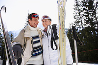 Skiing couple holding skis standing in mountains