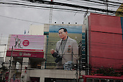 Au milieu de fils électriques, sous l'orage, le portrait du Roi Bumibhol en plein de centre de Bangkok sur l'avenue Ratchaprasong.