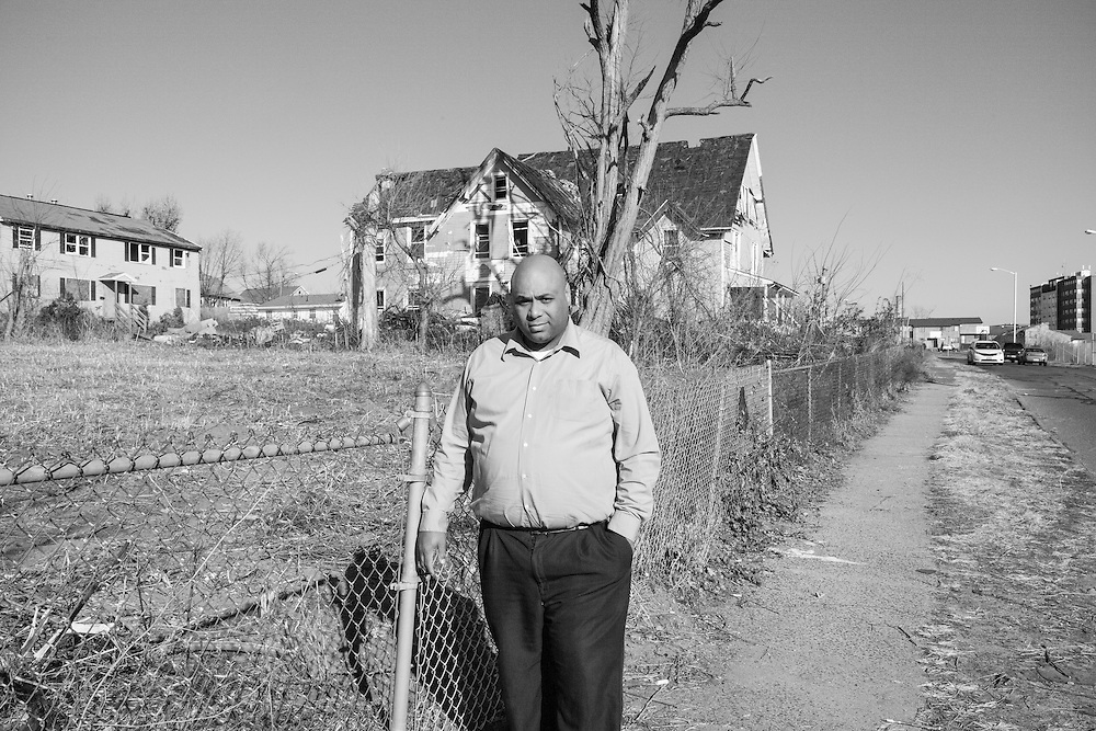 Michael Runnells standing next to a fence with open field and damaged residence behind him. Michael and family are still in transition from temporary housing to permanent housing.