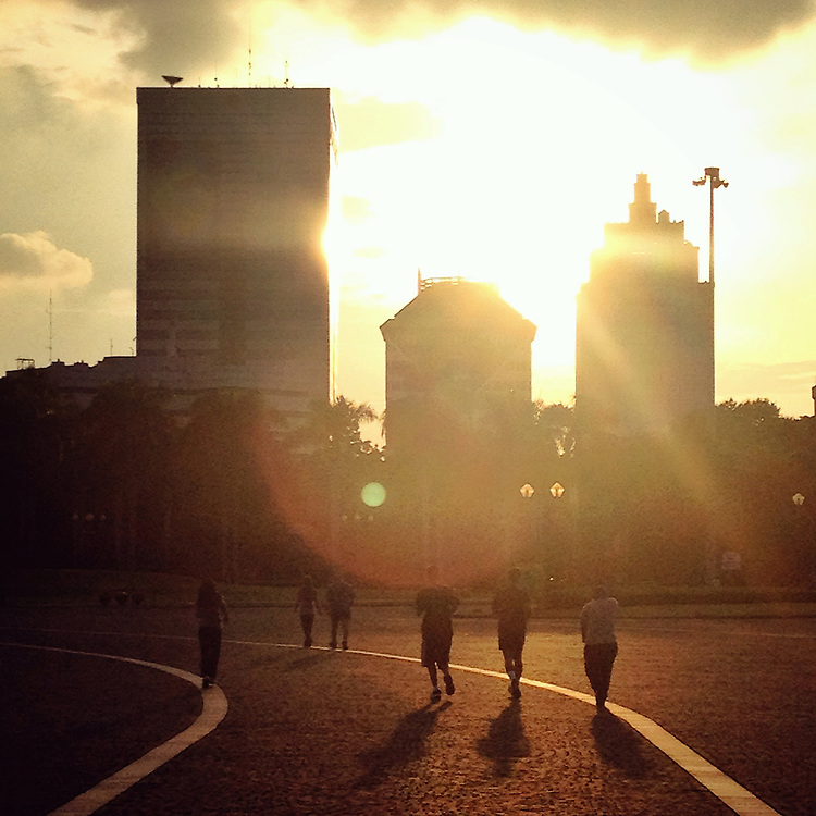 Joggers' silhouettes as they run around Monas Square at sunset.