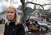 Beth Skudin outside her home in Long Beach, N.Y. on Thursday, Nov. 1, 2012 where all her belongings destroyed by the flooding caused by Hurricane Sandy are piled on the sidewalk. Skudin was rescued by jetski from the window of her home when flood waters threatened to overtake her.  (AP Photo/Kathy Kmonicek)