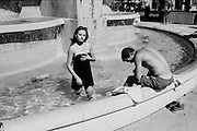 A young woman and a young man coooling off on a hot day in a fountain in Paris.