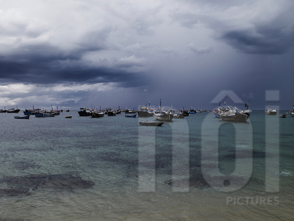 Fishing boats are anchored along the shore. A storm is coming over the harbour. Tuy Hoa, Vietnam, Asia.
