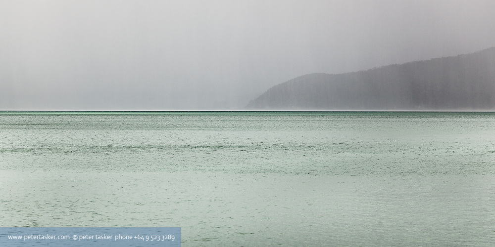 Looking down the Waiheke Channel while at anchor in Opopo Bay. Unusual light and colours as a result of changable weather.  Waiheke Island visible through the rain.