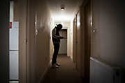 An unaccompanied minor refugee child stands in his hallway chatting with friends on his phone in his room where he has been recently housed. United Kingdom. (photo by Andrew Aitchison / In pictures via Getty Images)