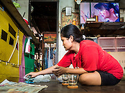 14 SEPTEMBER 2015 - BANGKOK, THAILAND:  A woman packs up some of her belongings in the home she's being evicted from. Fiftyfour homes around Wat Kalayanamit, a historic Buddhist temple on the Chao Phraya River in the Thonburi section of Bangkok are being razed and the residents evicted to make way for new development at the temple. The abbot of the temple said he was evicting the residents, who have lived on the temple grounds for generations, because their homes are unsafe and because he wants to improve the temple grounds. The evictions are a part of a Bangkok trend, especially along the Chao Phraya River and BTS light rail lines. Low income people are being evicted from their long time homes to make way for urban renewal.           PHOTO BY JACK KURTZ
