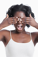 Playful young woman covering eyes and shouting against white background