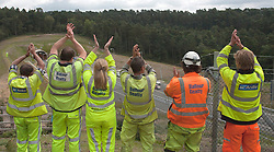 © Licensed to London News Pictures. 27/07/2011. Hindhead, Surrey, UK. Today (Wednesday) The £371 Million Hindhead Tunnel project officially opens to the public. Pictures: A selection of the 1000's of workers that constructed this project over a 4-year period, clap their hands as the tunnel officially opens to the public and the first vehicles emerge from the exit of the South Portal. Photo credit: Sam Spickett/LNP