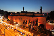 Grand Mosque or Ulu Cami seen at night behind a busy road, built 1396-99 under the Ottoman Sultan Bayezid I by the architect Ali Neccar in the Seljuk style, Bursa, Turkey. It is a large rectangular building with 2 minarets, and 20 domes supported by 12 columns. Supposedly the 20 domes were built instead of the 20 separate mosques which Sultan Bayezid I had promised for winning the Battle of Nicopolis in 1396. The mosque is in the old city centre of Bursa and remains the largest mosque in the city. Picture by Manuel Cohen