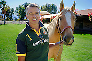 Handsome polo player standing in front of his horse holding horses reins on a sunny day. Stable is in background.