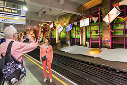 "© Licensed to London News Pictures. 07/06/2018. LONDON, UK.  Tourists view a new artwork ""my name is lettie eggyscrub"", by British artist Heather Phillipson, unveiled at Gloucester Road Underground station filling the 80m platform.  The installation is a major commission for Art on the Underground.  Photo credit: Stephen Chung/LNP"