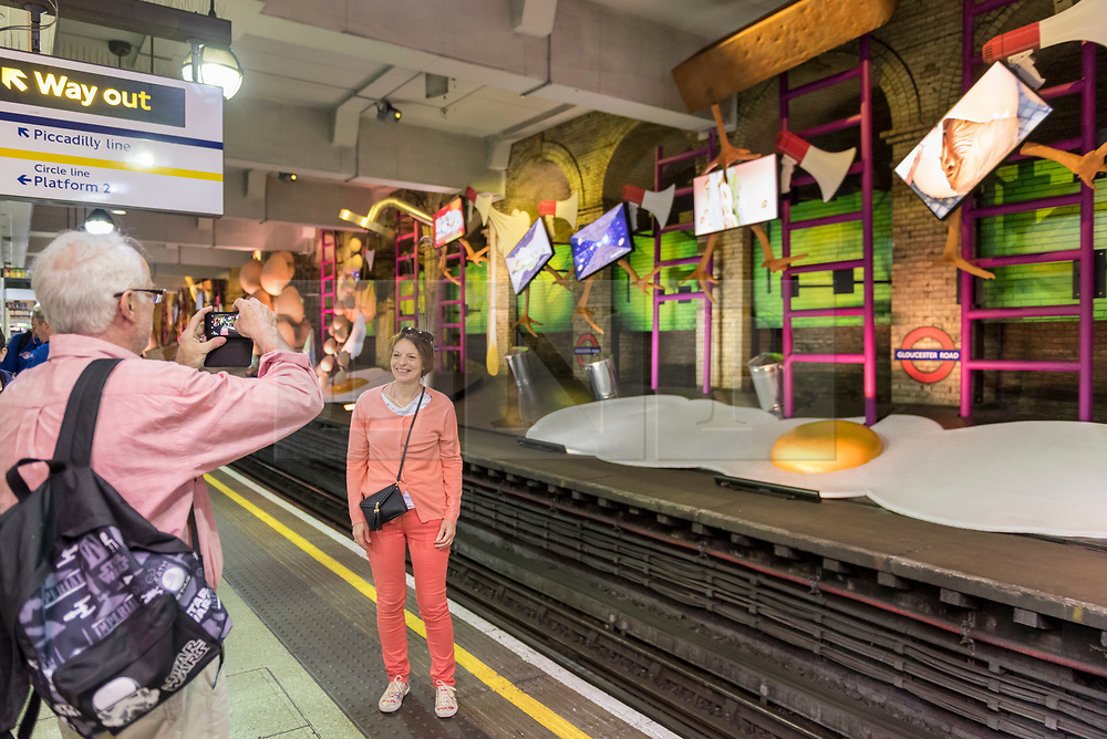 """© Licensed to London News Pictures. 07/06/2018. LONDON, UK.  Tourists view a new artwork """"my name is lettie eggyscrub"""", by British artist Heather Phillipson, unveiled at Gloucester Road Underground station filling the 80m platform.  The installation is a major commission for Art on the Underground.  Photo credit: Stephen Chung/LNP"""