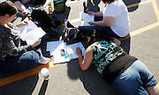"""People fill out applications as they wait in line for an open casting session for season 11 of """"The Biggest Loser"""" television show studies the application for the show in Broomfield, Colorado July 17, 2010. Over 600, many spending the night on the sidewalk outside the hall applied for a chance to be on the show and win $250,000.  REUTERS/Rick Wilking (UNITED STATES)"""