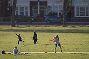 In the third week of the UK government's lockdown during the Coronavirus pandemic, when the daily UK death rate rose by another 761 to 12,868 and with nearly 100,000 reported cases. a London family play cricket during their teir daily exercises in Ruskin Park, a public green space in the south London borough of Lambeth, on 15th April 2020, on 15th April 2020, in London, England.