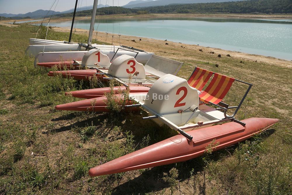 3 paddle boats and a catamaran waiting at water edge