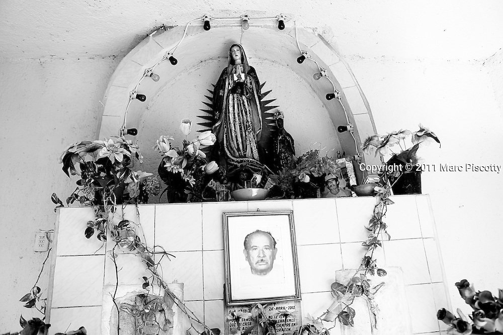 SHOT 11/16/11 1:13:44 PM - A roadside capilla featuring Our Lady of Guadalupe and pictures of loved ones along Carretera Federal 180 near Xcalacoop, Mexico. Roadside capillas, or tiny chapels, in the Mexican state of Quintana Roo. The capillas are common along the roads and highways of Mexico which is heavily Catholic and are often dedicated to certain patron saints or to the memory of a loved one that has passed away. Often times they contain prayer candles, pictures, personal artifacts or notes. (Photo by Marc Piscotty / © 2011)