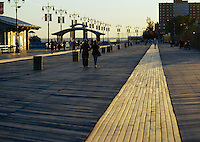 People enjoying the boardwalk in Coney Island at sunset, Brooklyn, New York.