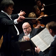 """November 21, 2013 - New York, NY : Conductor Alan Gilbert, left, leads the New York Philharmonic and soloists Philip Myers, on horn at front center, and tenor Michael Slattery, standing at foreground right, in Bejamin Britten's """"Serenade for Tenor, Horn, and Strings, Op. 31 (1943)"""" at Avery Fisher Hall at Lincoln Center on Thursday night. Slattery made his NY Phil debut as a last-minute substitution for tenor Paul Appleby, who withdrew due to illness. CREDIT: Karsten Moran for The New York Times"""